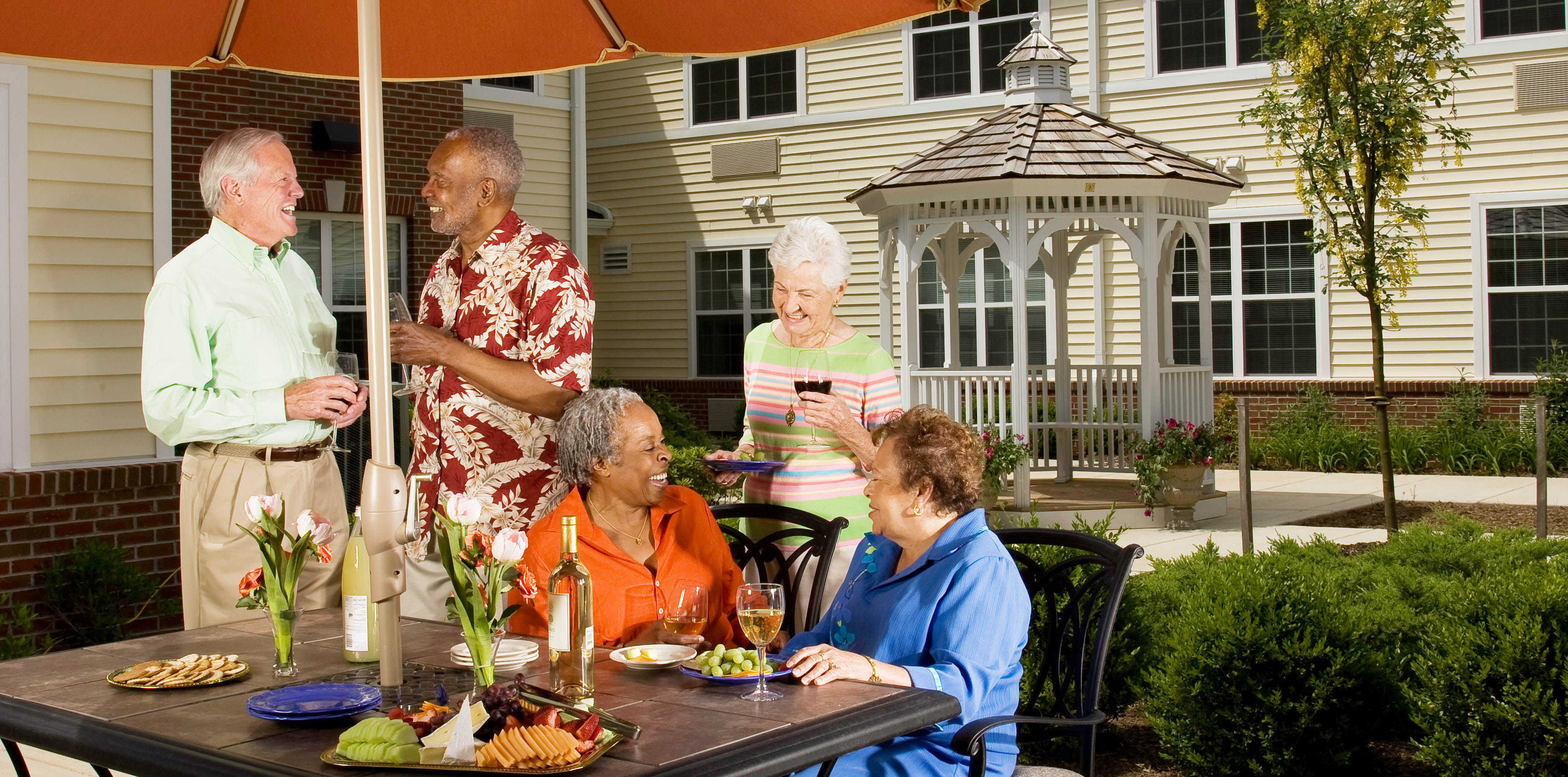 A group of senior residents enjoying the courtyard and snacks.